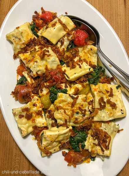 Maultaschen mit Spinat, geschmolzenen Tomaten und Röstzwiebeln