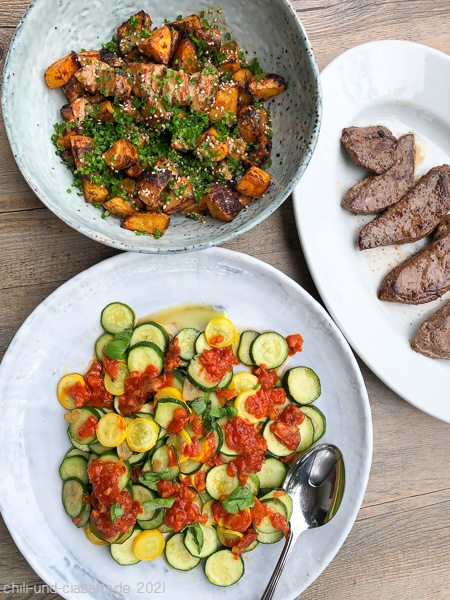 Rehschnitzel, Tahini-Röstkartoffeln und Zucchini mit Harissa